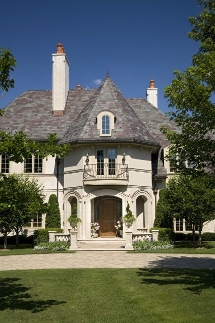A romantic fairy tale of a house with a turreted entrance reminiscent of old European castles and chateaux (via John Kraemer & Sons)
