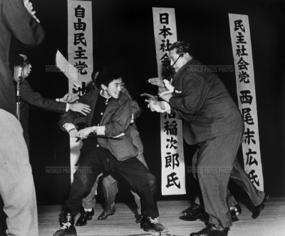 A right-wing student assassinates Inejiro Asanuma, Socialist Party Chairman, during his speech at the Hibiya Hall.  Year: 1960 Photographer: Yasushi Nagao Country: Tokyo, Japan