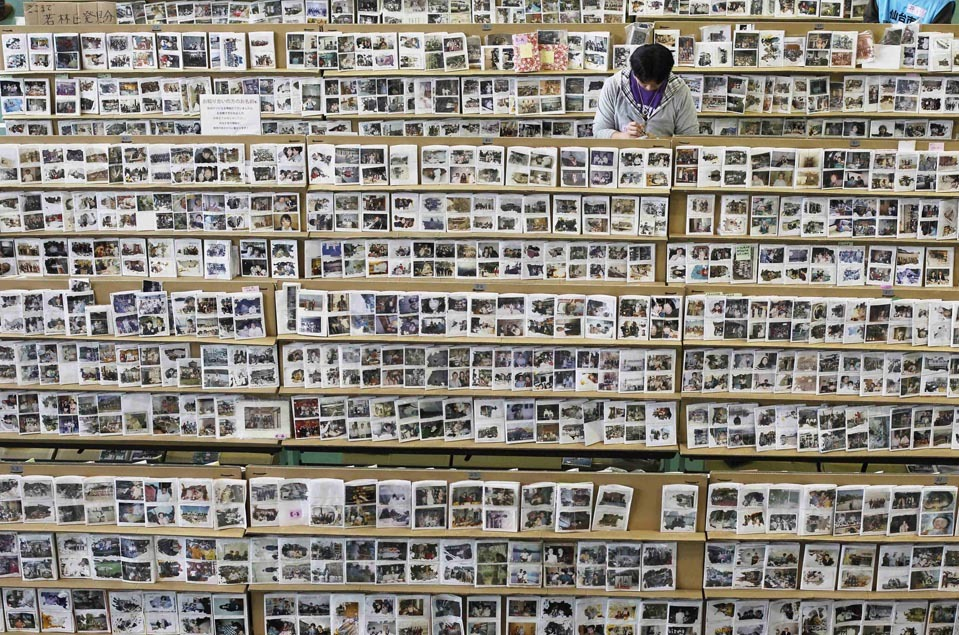 A man looked for his photographs at a collection center Friday, March 9 in Sendai, Japan, for items found after the March 11, 2011, earthquake and tsunami. A year later, more than 250,000 photographs and personal belongings on display for owners to recover. [Credit : Toru Hanai/Reuters]