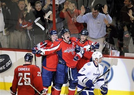 Washington Capitals left wing Alex Ovechkin, center, of Russia, screams and celebrates his game-winning goal with teammates Mike Green, right, Dmitry Orlov, of Russia, second from left, and Jason Chimera (25) as Tampa Bay Lightning defenseman Brett Clark (7) skates away during the overtime period of an NHL hockey game, Thursday, March 8, 2012, in Washington. The Capitals won 3-2 in overtime.