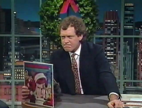 "David Letterman holding Six Million Dollar Man ""4 Exciting Christmas Adventures"""