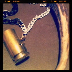 Deer antler point necklace with bullet shell.