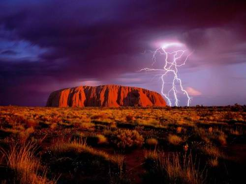 Ayers Rock in Uluru National Park Photograph by Mark Laricchia/Corbis Lightning flashes over Ayers Rock, a landmark red sandstone monolith that draws tourists to Australia's center. Uluru-Kata Tjuta National Park houses the rock, called Uluru by Aborigines, the continent's original inhabitants.