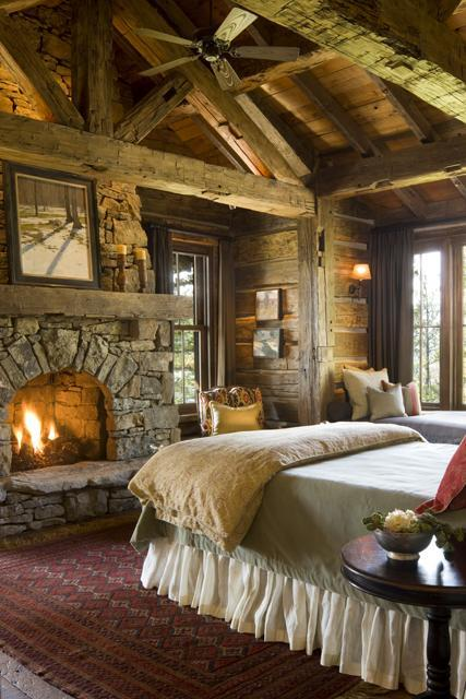 A wonderful rustic lodge bedroom with a fireplace and window seat (via Miller Architects)