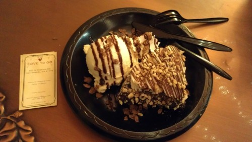 Chocolate-dipped waffle and ice cream topped with peanuts, corn flakes and caramel