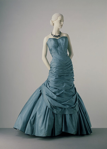 Charles James | c. 1955 The inspiration for this elegant evening dress probably came from cuirasse bodices and bustle skirts of the 1870s. James was fascinated by the cut of historical dress and explored innovative new forms of garment construction, such as spiral draping. His forte included the creation of luxurious, full-skirted evening gowns. He looked on dresses as works of art, as did his customers.