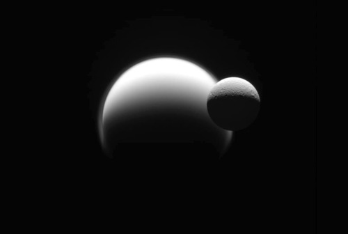 Rhea passes in front of the much larger haze-shrouded moon Titan, both in orbit around Saturn. (NASA/JPL) #