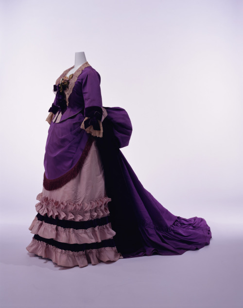 "c. 1874 Worth (obviously!) KCI says: A bustle style is a look that emerged immediately after the crinoline. Bright purple became fashionable with the invention of the chemical dye aniline in 1856. The usage of fashionable color and the generous drapery used in this dress are characterized of Maison Worth.  Charles Frederick Worth (1825-1895), an Englishman by origins, went on to establish his own maison in Paris in 1858. He set up the basis of the fashion system that would later be known as ""Haute Couture"" through initiatives such as showing his new designs on living women, developing clients who were fashion leaders in society, and implementing skillful advertising strategies. All of these ideas contributed to establishing Paris as the fashion capital of the late 19th Century."