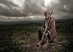 "Poor Kaffa tribe man on the road, Ethiopia by Eric Lafforgue on Flickr. ""I saw this man standing in a field in the countryside, not far from Addis. He had a spear with him, as he told me that baboons are sometimes agressive with the farmers! Many foreigner companies (turkish, holland, chinese..) come to open flowers plantations in Ethiopia, as the land costs nothing, and the average salary is only 1 euro a day…So even if the countryside looks more modern in many places, the people who works still earn few money and are still very poor… I used a ringfash on the right side. In fact a half ring flash as it was broken…Canon power!"""