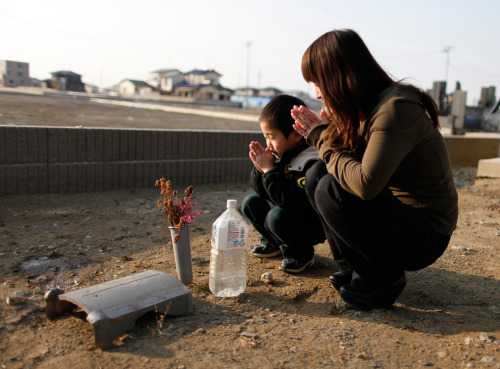 Yuko Sugimoto and her son Raito pray on February 22, 2012 at the site where their pet dog was buried in the yard of their house in Ishinomaki, Miyagi Prefecture, Japan after the 3011 earthquake and tsunami. (Yuriko Nakao/Reuters)  (via Japan tsunami pictures: before and after - The Big Picture - Boston.com)