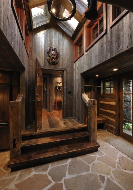 A gorgeous foyer of dark wood and stone with clerestory windows (via Lake Country Builders)