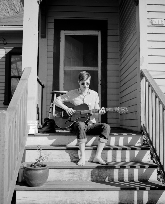 my neighbor picking his guitar in the sun. Portland, Oregon
