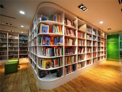 booksmut:  This white bookshelf design extends around the room to take advantage of existing space. Pretty!