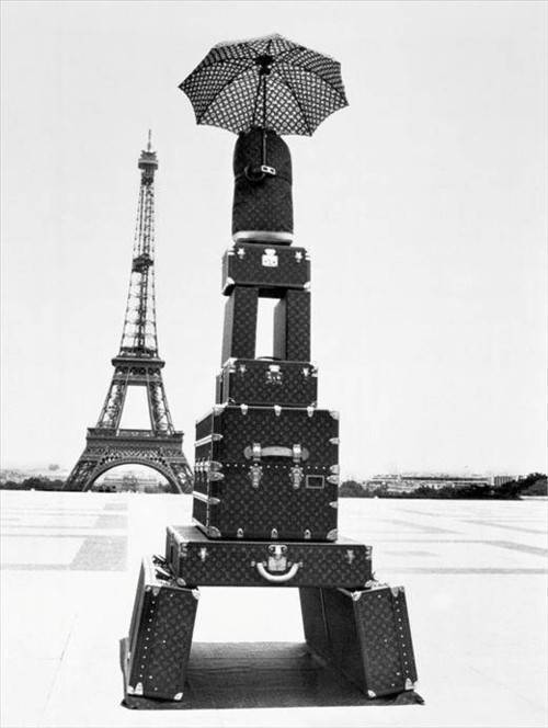 An imitation of the Eiffel Tower made of suitcases in front of the Eiffel Tower (or La Tour Eiffel, La dame de fer, the iron lady) i