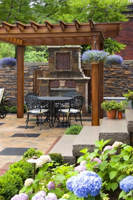 Backyard beauty - a pergola, fireplace, and wrought iron seating set make for a charming garden spot (via K West Images, Interior and Garden Photography)