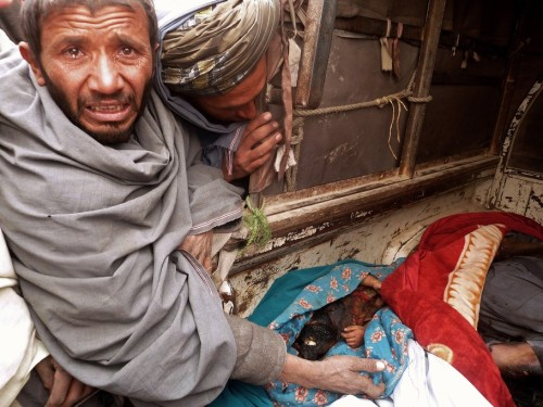 "A mourner cries over the bodies of Afghan civilians, allegedly shot by a rogue US soldier, seen loaded into the back of a truck in Alkozai village of Panjwayi district, Kandahar province on March 11, 2012. An AFP reporter counted 16 bodies — including women and children — in three Afghan houses after a rogue US soldier walked out of his base and began shooting civilians early Sunday. NATO's International Security Assistance Force said it had arrested a soldier ""in connection to an incident that resulted in Afghan casualties in Kandahar province"", without giving a figure for the dead or wounded. AFP PHOTO/ JANGIR"