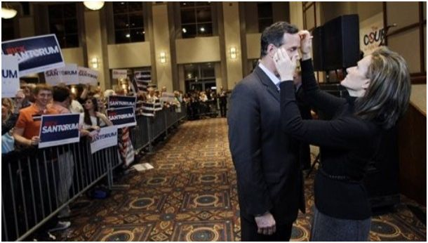 Bag's Take-Away: So far, Santorum's wife has stayed below the radar. Photos like this, however, and her influence on him, start to open up the subject. via DayLife (photo credit: Eric Gay/AP caption:  Karen Santorum, right, helps prepare her husband, Republican presidential candidate, former Pennsylvania Sen. Rick Santorum, for a live interview following a rally, Monday, March 12, 2012, in Montgomery, Ala.) Visit BagNewsNotes: Today's Media Images Analyzed ————— Topping LIFE.com's 2011 list of Best Photo Blogs, follow us at: BagNewsNotes; BAG Twitter; BAG Facebook; Bag by Email.