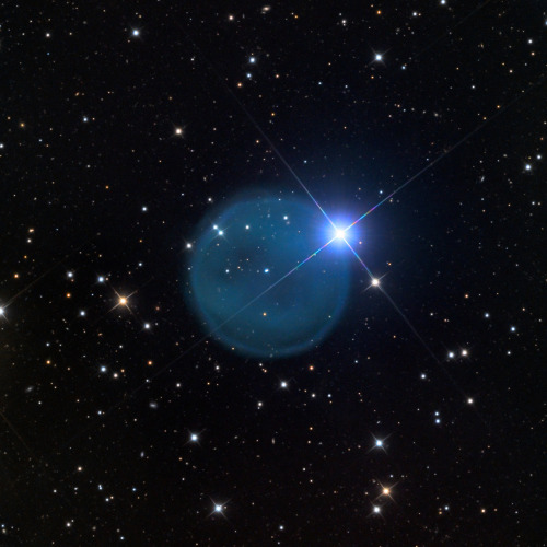 "Abell 33: an enigmatic blue bubble in space Planetary nebulae are the eerie and beautiful structures created when dying stars cast off their outer layers. They come in many strange shapes, and oddly it's quite rare to find one that appears perfectly circular such as Abell 33, located something like 1500 light years away. The central star may be a binary, two stars orbiting each other no closer than about 0.03 light years from each other — about 2000 times the distance of the Earth from the Sun. The central star(s) is off-center, which usually happen if the star is moving rapidly through space. The wind it expels gets ""blown back"" by gas in between the stars. The outer rim is nearly a perfect circle, which is really uncommon for planetary nebulae. Most are oval, or barrel-shaped, or something even weirder. It has to do with the way the dying star blows off winds, streams of subatomic particles from its surface. While rim is circular, the fog on the inside is not. It has two oval holes in it, slightly off center. Moreover, the two ovals are parallel, slanted a bit at the same angle. This may be a sign that the nebula itself may be more barrel shaped, and the two dark ovals are the open ends of the barrel structure. The bright star on the edge of it giving it a diamond-ring look is almost certainly just a chance alignment. It's probably much closer or farther away than the nebula, and coincidentally lined up."