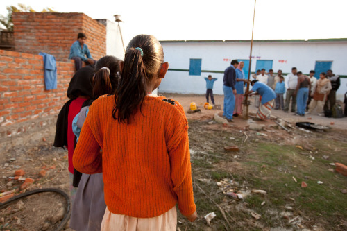 School girls look on as well mechanics fix a broken well. Learn more about sustainable water access in India at www.theadventureproject.org.