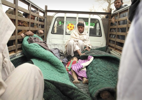 A man sits in the back of a truck with the bodies of several men and a child allegedly killed by a U.S. service member in Panjwai, Kandahar province south of Kabul, Afghanistan, Sunday, March 11, 2012. A U.S. service member walked out of a base in southern Afghanistan before dawn Sunday and started shooting Afghan civilians, according to villagers and Afghan and NATO officials. Villagers showed an Associated Press photographer 15 bodies, including women and children, and alleged they were killed by the American. (AP Photo/Allauddin Khan)