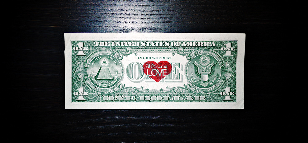 "SKYE NICOLAS, Buy Some Love, 2012Red ink on U.S. currency dollar bill2.6 x 6.14 in (6.63 x 15.60 cm) BUY SOME LOVERe-assigning the monetary value of actual currency An artist and a wealthy Russian art collector were having drinks at a hotel bar after having attended an art auction earlier that evening. Upon paying for their beverages, an unusual dollar bill slips out of the artist's wallet that catches the ever curious eye of the wealthy art collector. ""What's this?"" he inquired, picking up the crisp dollar bill. ""New work"" said the artist smiling. The back of the fresh note had been embellished with a small red heart, ink-stamped right at the center of the U.S. dollar note. It simply read ""Buy some Love"", rendered in a pleasing greeting-card-like font. The art collector paused to relish this playful little piece of art that he now carefully held with the tip of his fingers at the edges. It began to tickle his impulsive art buying senses, activating a familiar excitement that stimulated his voracity and passion for art collecting. ""I love it!"" he declared. ""It's simple, incredibly witty, and says so many things on so many levels. How much?"", he asked the artist as he sifted through his luxurious but slightly tacky calf skin leather wallet. ""I have… five hundred, fifty-three dollars! Please, I must have this."" A few days later, the delighted art collector proudly displayed the heart-stamped dollar bill (now signed by the artist) encased in a lovely glass box that rested on his precisely organized office desk. That same day, an upper east side heiress ordered a heavily sweetened latte at Starbucks. She is handed a receipt along with her change which included another dollar bill stamped with the same little red heart that had charmed the Russian art collector. ""Buy some Love"", it read. It spoke with serendipitous irony that made the heiress think of her petulant ex-husband whom she recently caught cheating on her with a high-class escort. Flustered and irate, she marched out onto the street and threw all her change including the heart-stamped dollar bill into the hat of a street performer who was playing a jazzy sax rendition of 'Can't Buy Me Love' by The Beatles. If a dollar bill was purchased for five hundred dollars as a work of art, would a hundred dollar bill stamped with the same little red heart be worth five thousand? Perhaps. This is what is so ludicrously fascinating about the world of modern contemporary art. Wealthy people will pay large sums of money for just about any piece of art they fancy, and simply because they can; even if it's what most people of the general public would identify as an ordinary dollar bill. Buy Some Love questions and challenges the concept of value and property, revealing playful irony and humor in the idea that an artist is capable of reassigning value, and in fact increasing the monetary value of actual currency, simply by transforming it into collectible art. Modern society seems to have been enslaved by the financial system, feeding on the visceral impulse that wealth can buy just about anything."