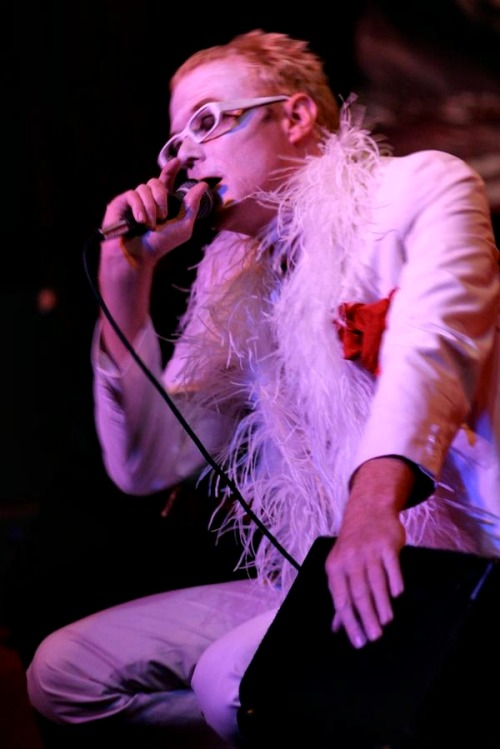 [Color photo of David J live on stage, in a white suit, white-framed glasses, white feather boa, and dapper red handkerchief]