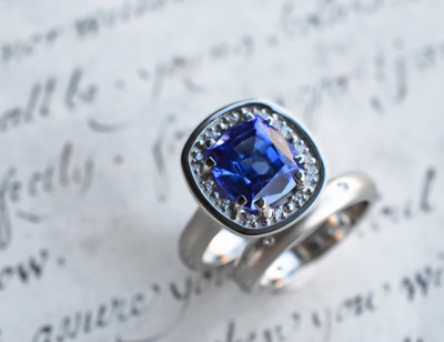 Cushion cut tanzanite in a 14k white gold and diamond custom setting.  Coordinating white gold, hammer-set diamond band.