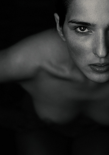Photographer Hannes Caspar shot this black and white, intense artistic nude portrait. I love how intense the stare of the model is and the depth of field being so shallow that only her face is sharp. The birds view enhances the intense stare of the mode. Hannes Caspar is a photographer from Berlin. He is also known as bluecut