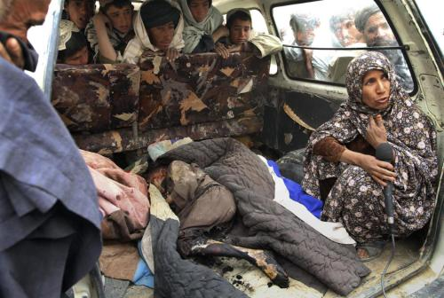 An Afghan woman, right, is interviewed as she sits next to the body of a child allegedly killed by a U.S. service member in Panjwai, Kandahar province south of Kabul, Afghanistan, Sunday, March 11, 2012. A U.S. service member walked out of a base in southern Afghanistan before dawn Sunday and started shooting Afghan civilians, according to villagers and Afghan and NATO officials. Villagers showed an Associated Press photographer 15 bodies, including women and children, and alleged they were killed by the American. (AP Photo/Allauddin Khan)