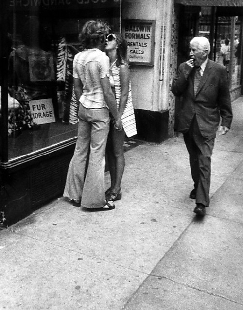 [Couple Kissing on Street, Man Walking By] Leon Levinstein