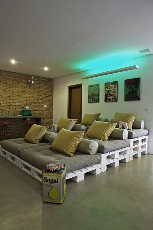 unconsumption:    In this installation, pallets are used as tiered seating in a media room. The pallets' open sides can be used as shelves for books, magazines, and other items. On the opposite wall, wall-mounted pallets set off a screen.