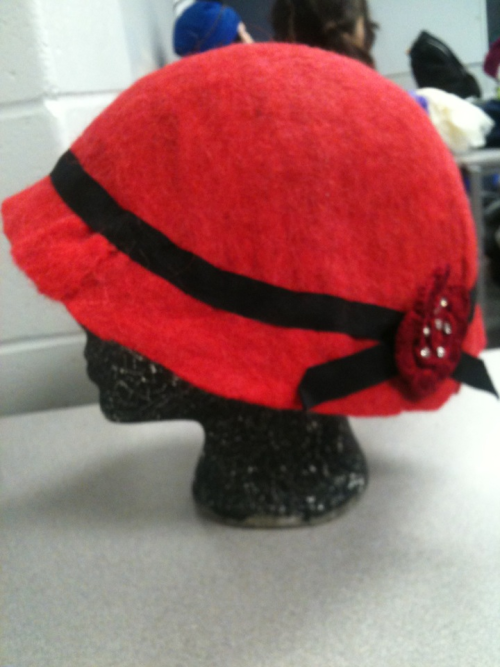 Felted 1920's inspired hat. It was a school project for my styles history class. I chose to make a hat the proper way, and made the felt myself and draped it over the form till I got the shape I wanted, and starched it for stiffness, did the same things to make the band, and then I hand stitches the pieces together.