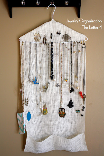 Organize Your Jewelry with The Letter 4 A hanger with some loosely woven fabric hung with some pockets (hand stitched or glued) and you have a jewelry organizer. Also, I am in blog love.