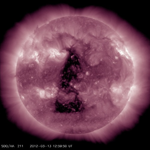 "wilwheaton:  moderation:  Huge Coronal Hole Is Sending Solar Wind Our Way — An enormous triangular hole in the Sun's corona was captured earlier today by NASA's Solar Dynamics Observatory, seen above from the AIA 211 imaging assembly. This gap in the Sun's atmosphere is allowing more charged solar particles to stream out into the Solar System… and toward Earth as well. Normally, loops of magnetic energy keep much of the Sun's outward flow of gas contained. Coronal holes are regions — sometimes very large regions, such as the one witnessed today — where the magnetic fields don't loop back onto the Sun but instead stream outwards, creating channels for solar material to escape. The material constantly flowing outward is called the solar wind, which typically ""blows"" at around 250 miles (400 km) per second. When a coronal hole is present, though, the wind speed can double to nearly 500 miles (800 km) per second. (via universetoday)  Holy shit, you guys. The Sun is the Eye of Sauron."