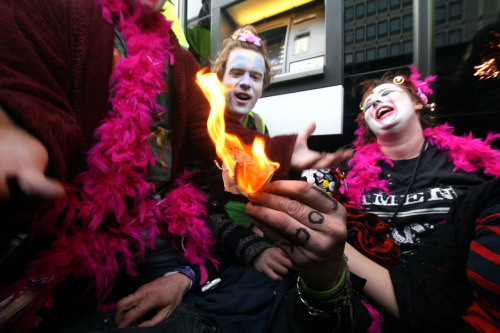 tompullenphoto:  Burning five English pounds infront of an HSBC banker during a student protest in central London, 14 March 2012. Copyright Tom Pullen.