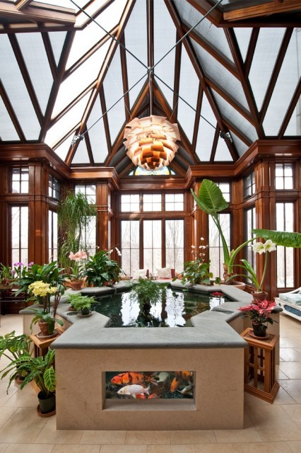 Amazing conservatory with a unique multi-vaulted ceiling, tall windows, and a koi pond (via Chase Building Group)