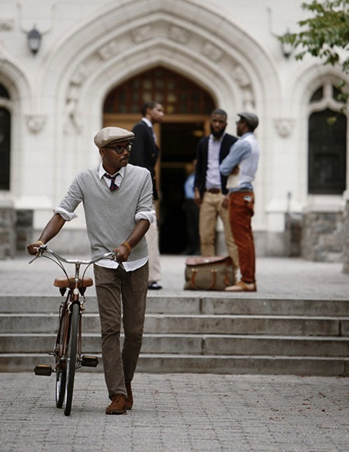 That bike is awesome, as are the outfits of the gentlemen depicted and the building in the background.