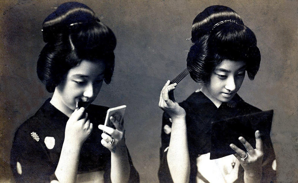 Two Geiko putting on make-up and fixing their hair, 1920s.