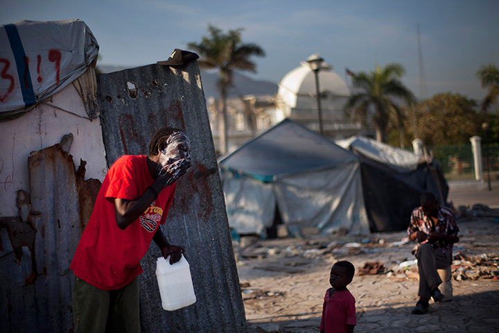 A man washes his face outside a makeshift shelter in front of the collapsed National Palace in Port-au-Prince, Haiti, March 14, 2012. [Credit : Ramon Espinosa/AP]