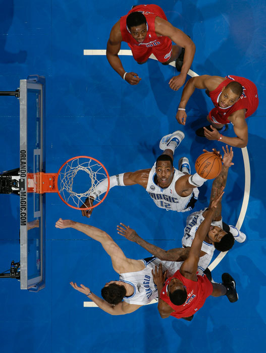 Magic center Dwight Howard battles in the paint for a rebound during a 2011 game against the Clippers. After weeks of wavering, Howard waived his early termination option and will stay with Orlando for the 2012-13 season. (Fernando Medina/Getty Images) GALLERY: Rare Photos of Magic center Dwight HowardAMICK: Howard changes course again, chooses to stay in OrlandoTRADE RUMORS: Get the latest trade buzz | Completed trades