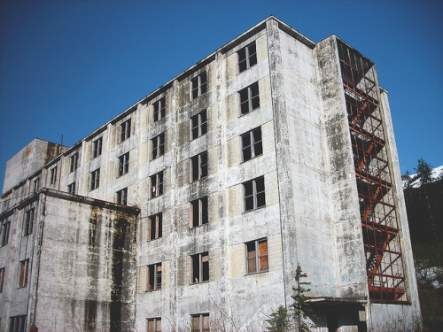 "wistful1:  The Buckner Building, Whittier, Alaska By Christopher Paul Williams on Flickr. Once the largest building in Alaska but was seriously damaged in the 9.2 1964 Alaska earthquake. It is now just a large, abandoned government building. Two factors combine to make safe demolition of the building cost-prohibitive: First, there is a potentially dangerous amount of asbestos in the building. Second, the only land-route in and out of Whittier is through the Anton Anderson Memorial Tunnel, so debris would either have to go through the tunnel or be moved on ships. The building is a local hang out for kids, and is often explored by tourists. The safety of the building is marginal, due to the asbestos and questionable structural integrity. Bears are often found inside the building in the spring, and it is full of ice and precariously dangling pipes, wires, and substructure. The floors are almost completely flooded, with at least one inch or more of water on each level. There are concrete staircases in the building. One is located near the garage and the others are in the middle of the structure. There are also fire exits on both sides, visible to the whole town. The stairwell leading to the basement is in total darkness and at the bottom of the stairwell is ""The Door"". Through the door is the basement which, although caved in, is still accessible.  I really really really wanna go back here. The parts I saw were pretty awesome."