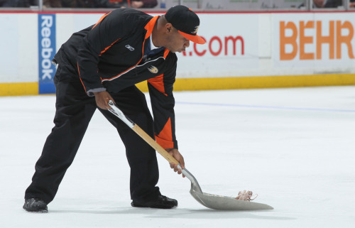 nationalpostsports:  SQUID ALERT! An arena crew worker shovels a squid off the ice in the third period of the game between the Detroit Red Wings and the Anaheim Ducks. The Ducks defeated the Red Wings 4-0.  (Photo by Victor Decolongon/Getty Images)