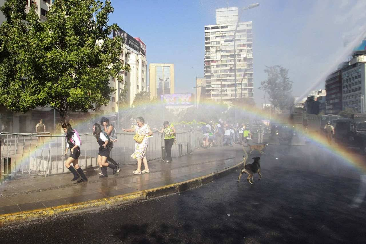 Student protesters and pedestrians run away from a jet of water released from a riot police vehicle during a demonstration against the government demanding changes in the public state education system in Santiago March 15, 2012.  Chilean students have been protesting against what they say is profiteering in the state education system. [REUTERS/Ivan Alvarado]