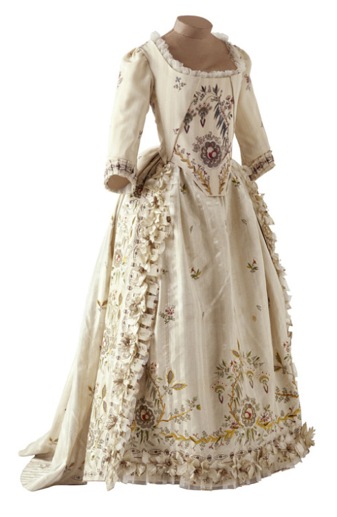 "Ballgown, 1780-85 France, Musée des Tissus de Lyon  This dress, also called ""robe parée"", is a ball dress. The skirt is worn over a pannier which, early 1780, was less ample than the one used under the dress ""à la française"". The decoration consists of appliqué painted flowers, gauze flounces and extremely refined embroideries. It exemplifies the dresses Rose Bertin, Marie-Antoinette's dressmaker, used to create for the queen."