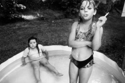 s-kulls:  Amanda and her cousin Amy, Valdese, North Carolina by Mary Ellen Mark North Carolina, USA, 1990In 1990, Peter Howe at Life magazine sent me to North Carolina to photograph a special school for children with problems. The school was a very strange place because all of the twenty or so children were in the same classroom and their problems ranged from mild behavior instability to severe schizophrenia.Nine-year-old Amanda was the most interesting child in the class. She was my favorite child. Amanda was very intelligent and very naughty. One day I followed her home on the school bus. When the bus stopped at her house, she dashed ahead of me and ran into a nearby wooded area. I continued to follow her into the woods and eventually found her sitting in an old stuffed chair having a cigarette. She thought that I would reprimand her since I was an adult. But I said nothing.The following Sunday, I spent the day at home with Amanda and her mother. Amanda totally controlled her mother. She constantly gave her orders and proceeded to put on her mother's nail polish and makeup. Amanda smoked openly in front of her. Her 8-year-old cousin Amy was coming over, and she was very excited. All day long, Amanda and her cousin played like children. Every forty-five minutes or so, Amanda would take a break to have a cigarette. Her mother could say nothing; Amanda was the boss.Just before I left, I looked for Amanda to say good-bye. I found her and Amy in the backyard. They were in a children's inflatable pool. Amanda was taking her regular cigarette break.