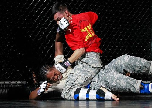 "Denied combat roles, Army women battle men in cage fighting: ""We can be as tough as the guys,"" says one who made it to a championship round of a tournament at Ft. Hood, Texas.  The Army still bars women from fighting in combat units. But some women are trying to break that barrier far from the front lines — by battling male soldiers in chain-link cages against a backdrop of strobe lights, thumping music and swirling smoke. The slugfests resemble ultimate fighting, a staple of pay-per-view television, right down to the black wire cages and throat-constricting holds with names like ""the guillotine"" and ""the rear naked choke.""  Photo: Staff Sgt. Jackelyn Walker takes blows to the face as she fights Pfc. Gregory Langarica in the bantamweight championship of the finals. Credit: José M. Osorio / Chicago Tribune"
