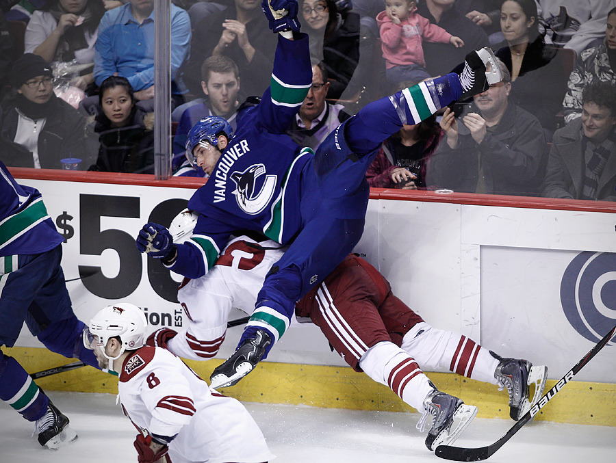Vancouver Canucks Ryan Kesler checks Phoenix Coyotes Antoine Vermette during the second period of their NHL hockey game in Vancouver, British Columbia March 14, 2012.   REUTERS/Ben Nelms    (CANADA)