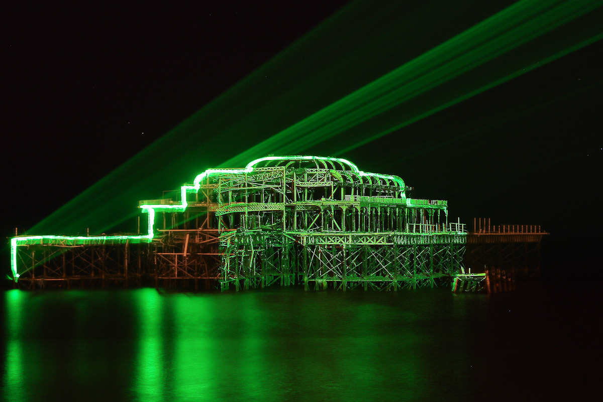 BRIGHTON WEST PIER LASER DISPLAY: a personal shot from the archive, taken in February 2010 Not sure what put this memory in my mind just now, but here's the burnt out old West Pier in Brighton, being lit by lasers one night in February 2010. I love Brighton - I lived there for about three years or so and it's a place where there is always something going on to get involved with or take photos of. This shot was an experiment in long exposures. The lasers were mostly tracking over the different bits of the pier - rarely lighting the whole thing at once. It produced a surreal, alien-landing sort of vibe down on the beach that night. This shot was a 25 second exposure and it's definitely weird but I like it. My flat was just a couple of minutes up the road from where this shot was taken - I miss that flat.