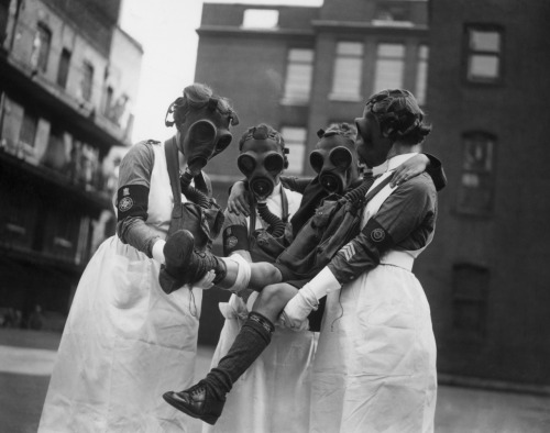 glukauf:  Nurses wearing gas masks attend to a patient, during a gas attack demonstration held at Toynbee hall, London, by the St John Ambulance Brigade,  28th September 1935.