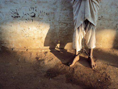 "dispirits:  ""I saw his feet, scarred by chains that also bound his hands. His eyes were resigned, his violence contained."" — by Reza (photographer)."